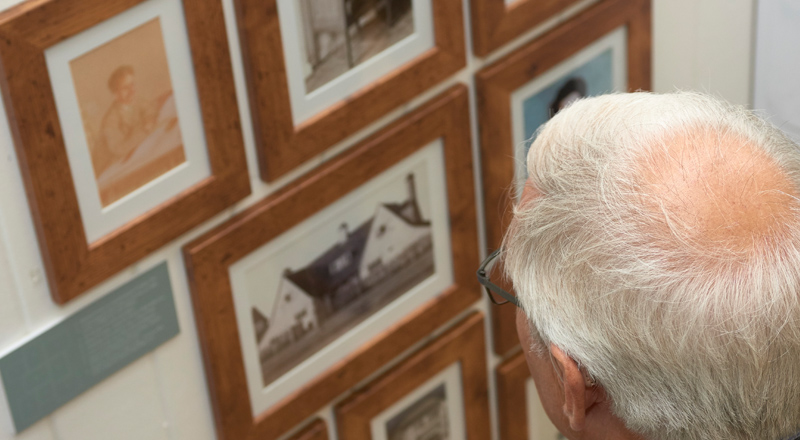 Image of man looking at photographs at Letchworth exhibition design