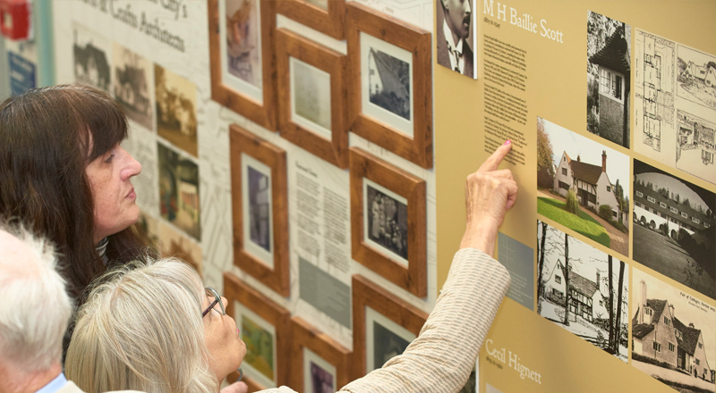 Image of woman pointing at information on exhibition design wall panel